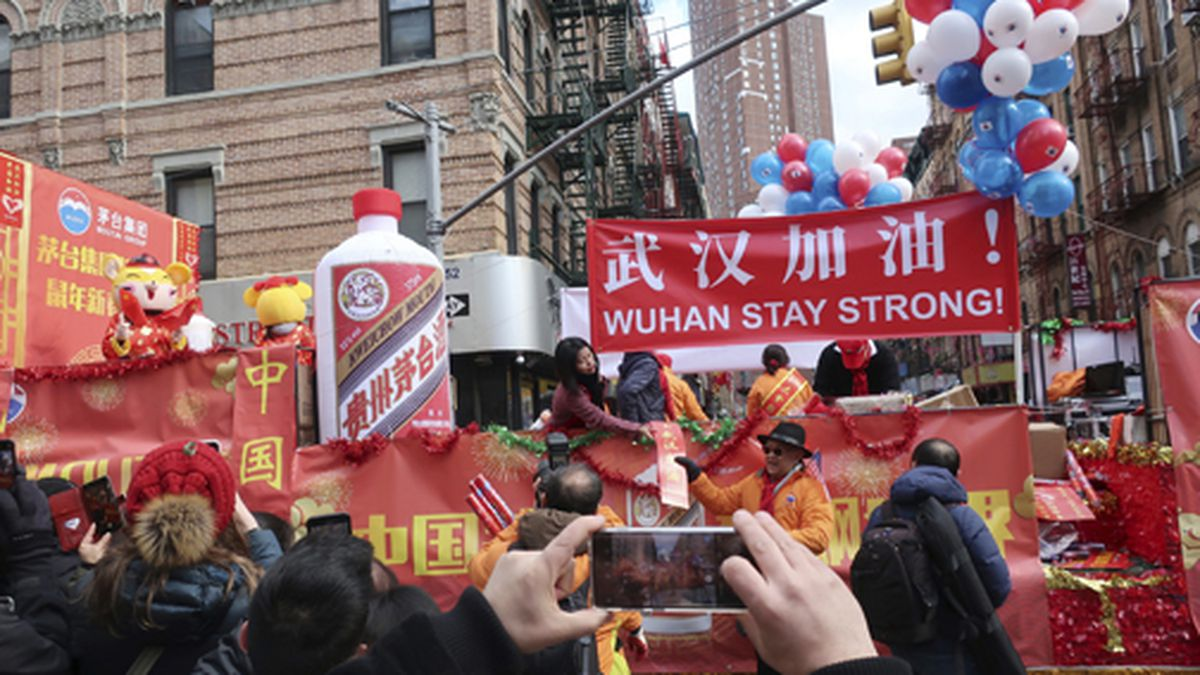 People display signs in support of Wuhan, China, at the center of the coronavirus outbreak, during the Lunar New Year parade, Sunday, Feb. 9, 2020, in Manhattan's Chinatown, in New York. (AP Photo/Ted Shaffrey)