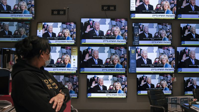 An Israeli electronics store employee looks at a wall of televisions broadcasting live the 59th...