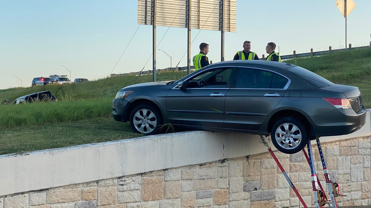 A crash on Highway 6 left a car partly hanging off a ledge of the overpass's embankment.