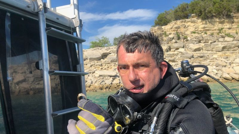 Diver Brian Waddell recovers Aggie ring 70 ft below the lake surface.
