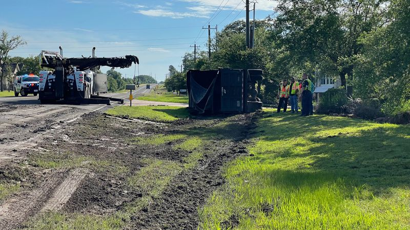 Authorities work to clean up road after dump truck turns over