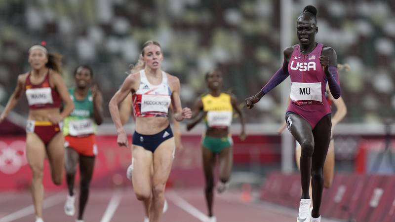 Athing Mu, right, of the United States, runs to the finish line to win the final of the women's...