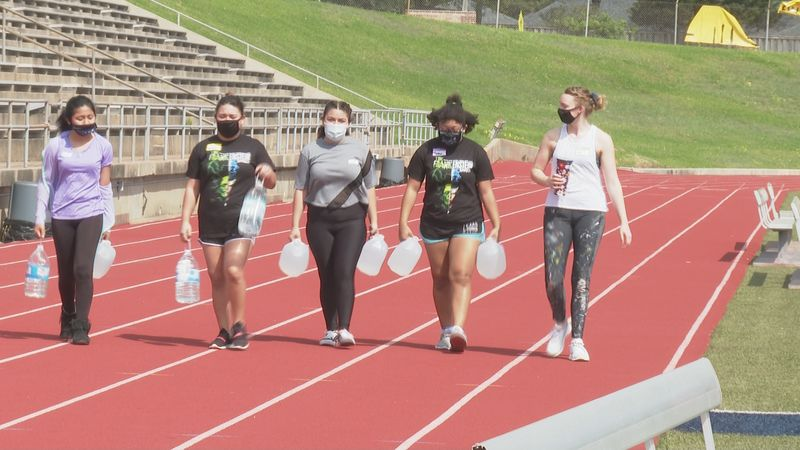 Bryan High students walking with water to raise awareness in water scarcity