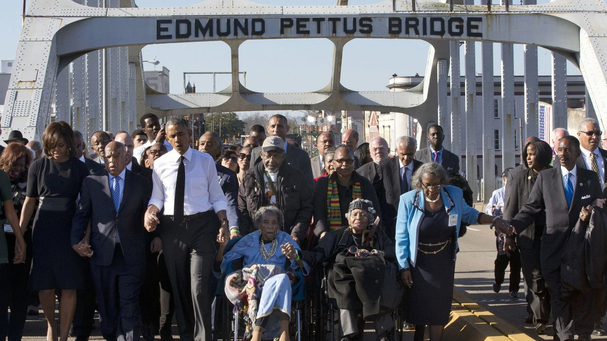 "In this March 7, 2015, file photo, singing ""We Shall Overcome,"" President Barack Obama, third from left, walks holding hands with Amelia Boynton, who was beaten during ""Bloody Sunday,"" as they and the first family and others including Rep. John Lewis, D-Ga, left of Obama, walk across the Edmund Pettus Bridge in Selma, Ala., for the 50th anniversary of ""Bloody Sunday,"" a landmark event of the civil rights movement. Some residents in the landmark civil rights city of Selma, Ala., are among the critics of a bid to rename the historic bridge where voting rights marchers were beaten in 1965."