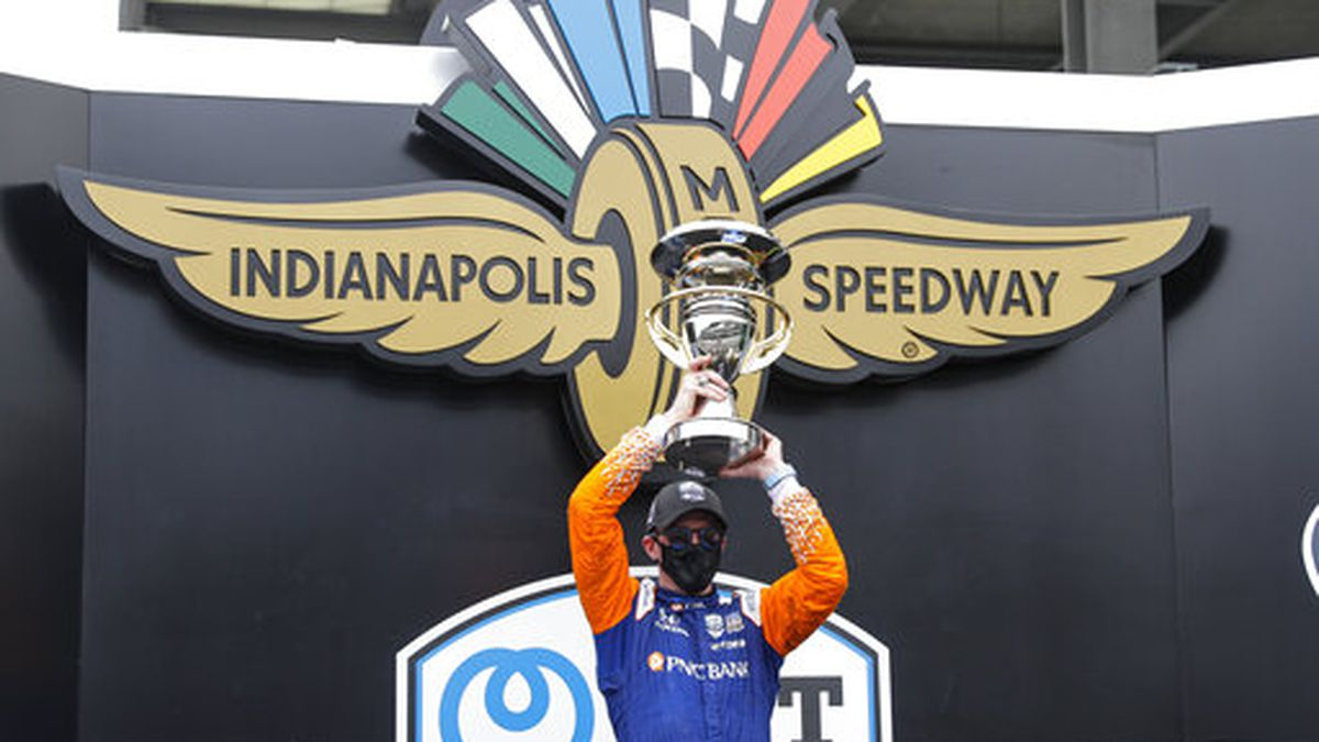 Race driver Scott Dixon, of New Zealand, celebrates with the trophy after winning the IndyCar auto race at Indianapolis Motor Speedway in Indianapolis, Saturday, July 4, 2020. (AP Photo/Darron Cummings)