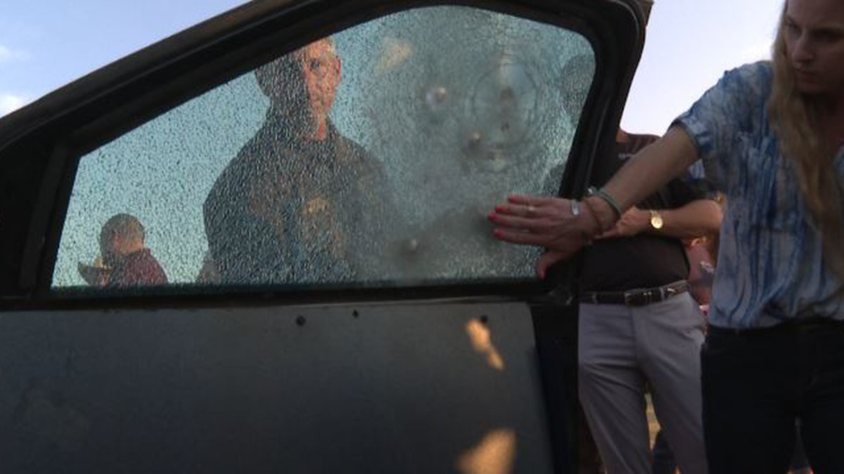 Spectators look at the bullet proof glass after a demonstration.