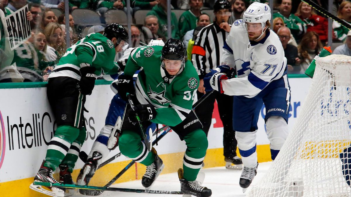 Dallas Stars right wing Denis Gurianov, left, and Tampa Bay Lightning center Anthony Cirelli, right, look to chase down a loose puck during an NHL hockey game in Dallas, Monday, Jan. 27, 2020. Dallas won, 3-2 in overtime.