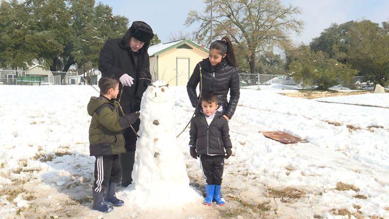 The Tirado Family of Bryan was building a snowman Monday.