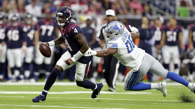 Houston Texans quarterback Deshaun Watson (4) breaks away from Detroit Lions defensive end...
