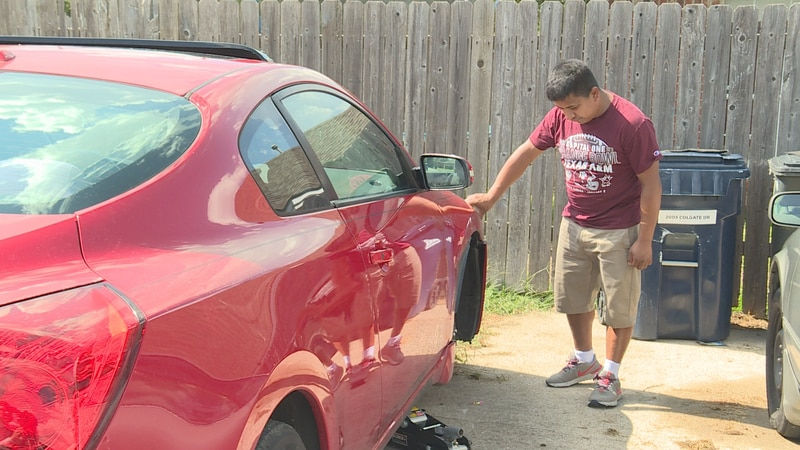 Francisco Roman surveys the damage done to his daughter's car after he says someone vandalized...