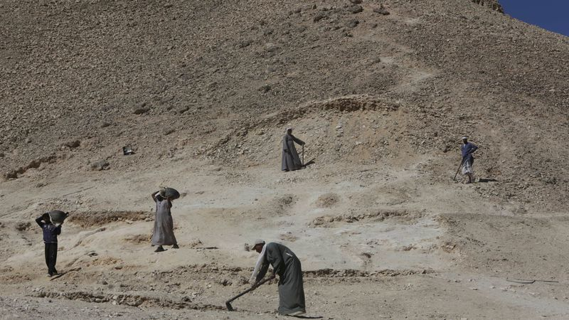 Egyptian excavation workers dig for antiquities in the Valley of the Kings in Luxor, Egypt,...