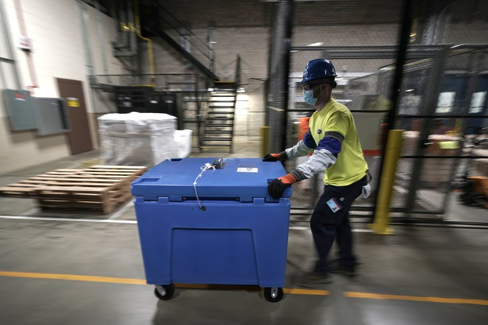 A worker transports a container carrying boxes of the Pfizer-BioNTech COVID-19 vaccine to be...