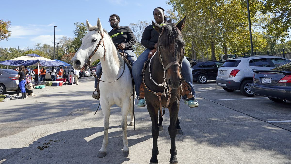 Eboni Price, right, and Cornelius Ates arrive on horseback to vote at a polling site Tuesday,...